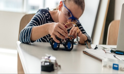 A young girl working on a robotic model car.